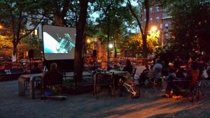 A movie screen is set up in a night scene in a park with people sitting in a crowd on lawn chairs.