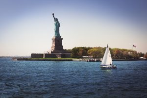 NY Harbor photo of the statue of Liberty in the middle of the water on Liberty Island and a sail boat.