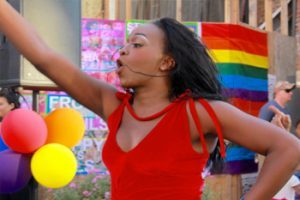 This is a photo of a girl wearing a red tank top on a crowded street with a pride flag waving in the background with balloons.