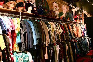 Interior shot of a vintage store showing one wall that has stacked clothing bars and a shelf with props above with mannequin heads with hats and tshirts hanging on the walls.
